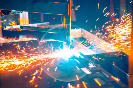 Plasma cutting machine burns through a thick sheet of steel by scattering drops of molten metal in different directions Standard-Bild