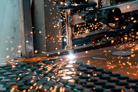 Plasma cutting machine burns through a thick sheet of steel by scattering drops of molten metal in different directions