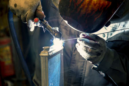 A TIG specialist welds a pipe to a small car radiator