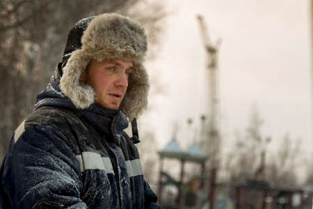 Portrait of a man in a hat with light fur with a blue winter jacket at the workplace
