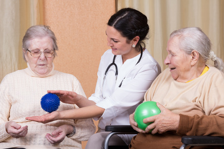 strength therapy: couple of senior Woman with physical therapists using fitness balls
