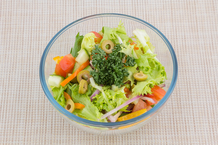 Bowl of healthy green garden salad with fresh vegetables from above