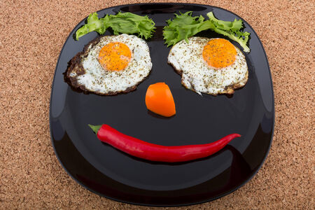 Smiling face made of fried eggs and vegetables on the plate Stock fotó