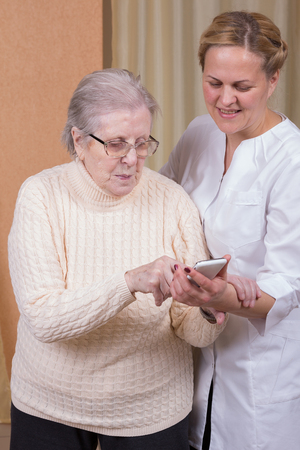Nurse helping elderly woman with cellphone Stock fotó