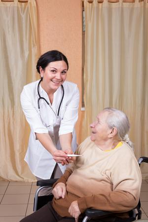 controling: Nurse and senior patient controling temperature Stock Photo