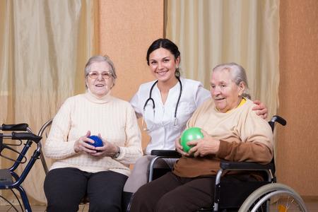 terapia ocupacional: pareja de la mujer mayor con fisioterapeutas que utilizan pelotas para ejercicios Foto de archivo