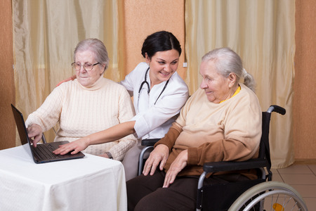 couple of senior Woman with carer Learning Computer Together