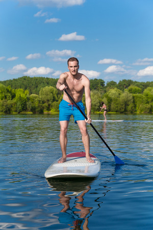 Young attractive man on stand up paddle board in the lake, SUP