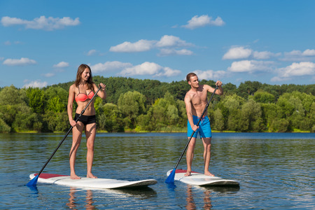 Young attractive couple on stand up paddle board in the lake, SUP Foto de archivo