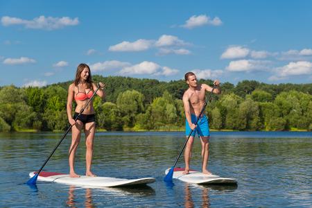 pizarra: Atractiva pareja joven en lev�ntese el tablero de paleta en el lago, SUP
