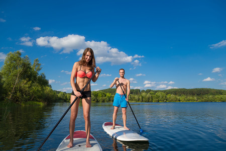 Young attractive couple on stand up paddle board in the lake, SUP 스톡 콘텐츠