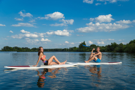 Young attractive couple sits on stand up paddle board in the lake, SUP Reklamní fotografie