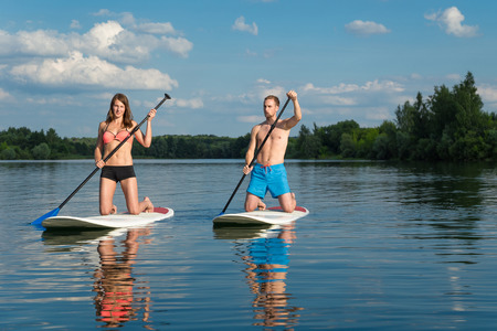 Young attractive couple knees on stand up paddle board in the lake, SUP