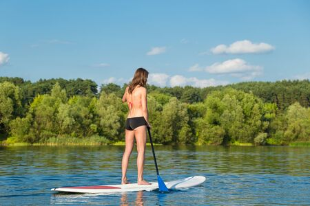 Young attractive woman on stand up paddle board in the lake, SUP Stock fotó