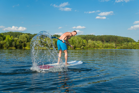 Young attractive man splashing water on stand up paddle board in the lake, SUP Reklamní fotografie