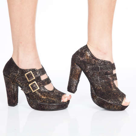 Heeled shoes women's shoes with straps and gold buckles on white background.
