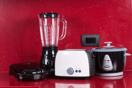 Household appliances in modern kitchen red background.