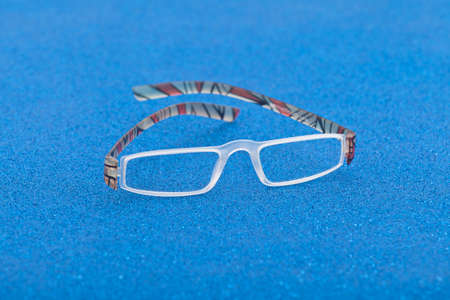 Fashion and style; eyeglasses on a blue background.