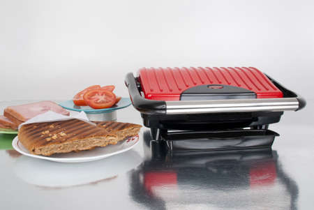 Household appliance red panini machine; Photo on neutral background.