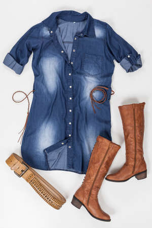 Indigo Fabric Dress With Buttons, Belt, And Brown Boots On White Background. Imagens