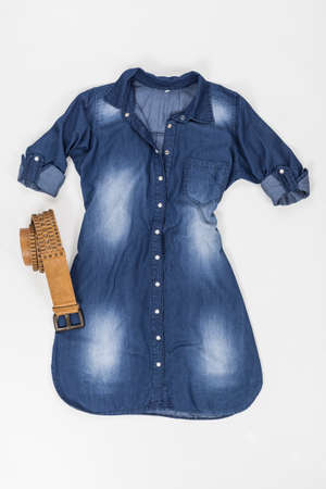 Indigo Fabric Dress With Buttons And Brown Belt On White Background.