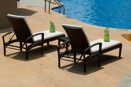 Lounge Chairs By The Swimming Pool. 免版税图像