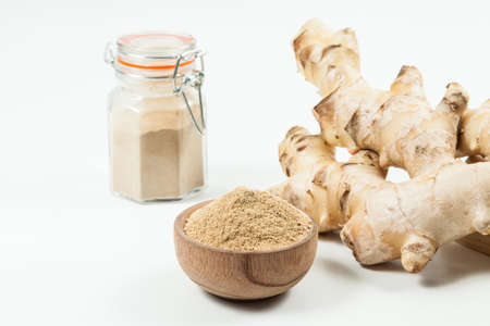 Fresh roots and ginger powder - Zingiber officinale; photo on wooden background.