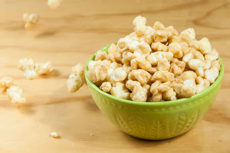 A Bowl Of Tasty Caramelized Popcorn; On Wooden Background.