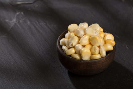 Zea mays - Wooden bowl with fresh corn kernels.