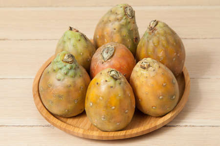 Prickly pear cactus fruits - Opuntia ficus indica; photo on wooden background.