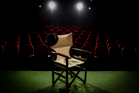 Director's chair on stage, in front of empty seats and in between curtains