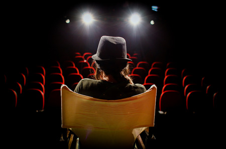 Young woman on director's chair on stage, in front of empty seats and in between curtains