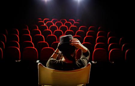 Młoda kobieta na krześle reżysera na scenie, przed pustymi siedzeniami i pomiędzy zasłonami