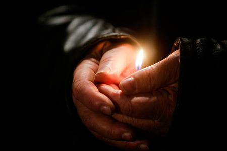 Person holding a wax candle in hands Stock Photo