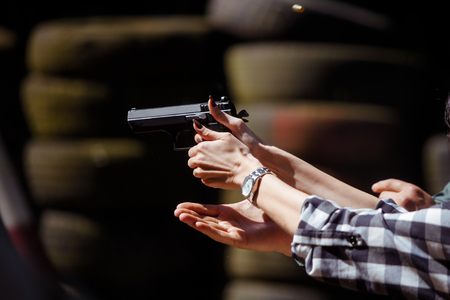 Young woman firing a 9 mm handgun in a shooting range Banco de Imagens