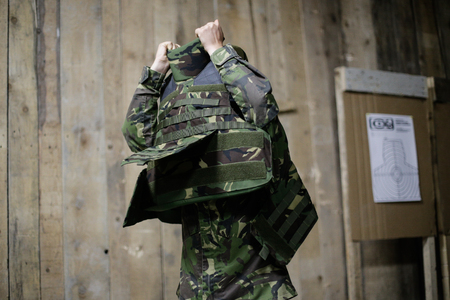 A female soldier puts on a bulletproof military vest