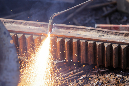 Worker uses oxy acetylene cutting torch at a scrapheap junkyard