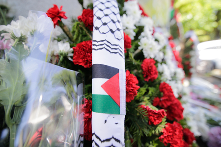 Flowers with the Palestinian flag and candles on the pavement