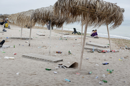 VAMA VECHE, ROMANIA - MAY 1, 2018: Young people rest on the beach amongst debris (especially empty bottles), after partying all night, early in the morning just before sunrise