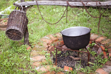 Wooden basket and a cast iron cauldron over a fire pit made from red bricks, in the backyard