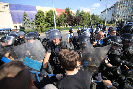 BUCHAREST, ROMANIA - August 10, 2018: Riot police spray teargas while scuffling with protesters outside the government headquarters. Romanians who live abroad are staging an anti-government protest calling on the left-wing government to resign and an earl