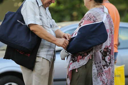 BUCHAREST, ROMANIA - August 13, 2018: Elderly couple walking from Floreasca Emergency Hospital, where the lady had her left arm put in a plaster cast
