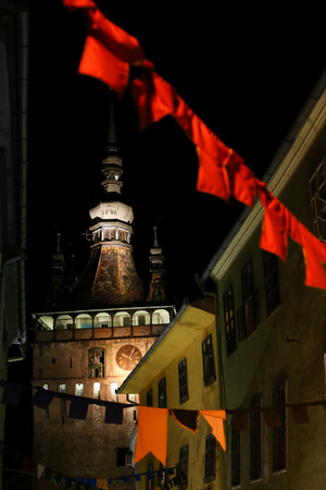 SIGHISOARA, ROMANIA - August 17, 2018: Night scene with the tower clock of the medieval town of Sighisoara, in Transylvania, Romania, in Sighisoara, on August 17 Редакционное