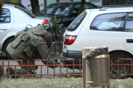 BUCHAREST, ROMANIA - August 31, 2018: Bomb Disposal Expert in Bomb suit for Explosive ordnance disposal (EOD) is verifying a suspect car on a street in Bucharest, on August 31.