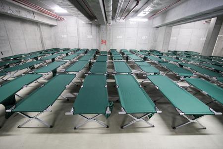 Camp-Klappbetten werden in der Tiefgarage eines Stadions aufgestellt und warten auf Flüchtlinge, während der Übung eines katastrophalen Erdbebens in der Stadt, in dem es viele Opfer gibt