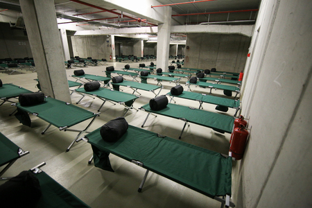 Camp folding cots and sleeping bags are being set up in the underground parking of a stadium and wait for refugees, during the drill of a catastrophic earthquake in the city in which there are many victims