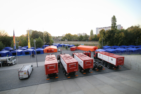 BUCHAREST, ROMANIA - October 15, 2018: Tents and fire trucks at a camp site for refugees during the drill of a catastrophic earthquake in the city in which there are many victims, at the National Arena Stadium in Bucharest. Imagens - 122359348