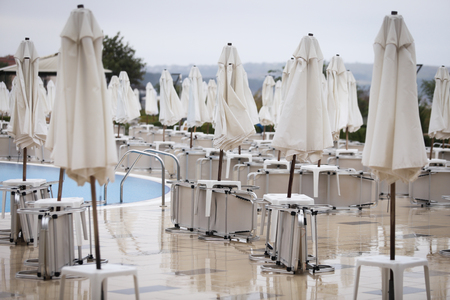 Closed sun umbrellas and lawn chairs around a hotel pool in off season, with no people in a cold cloudy day, in late autumn on the Bulgarian seaside