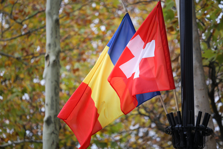 Romania and Switzerland flags waving on a pole, with trees and autumn brown and yellow leaves on background Stock Photo
