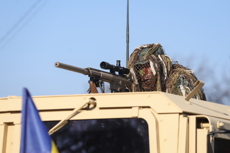 Bucharest, Romania - December 1, 2018: Romanian army sniper, armed with the US M110 semi-automatic sniper rifle and on top of a Humvee armored vehicle, at the Romanian National Day military parade.